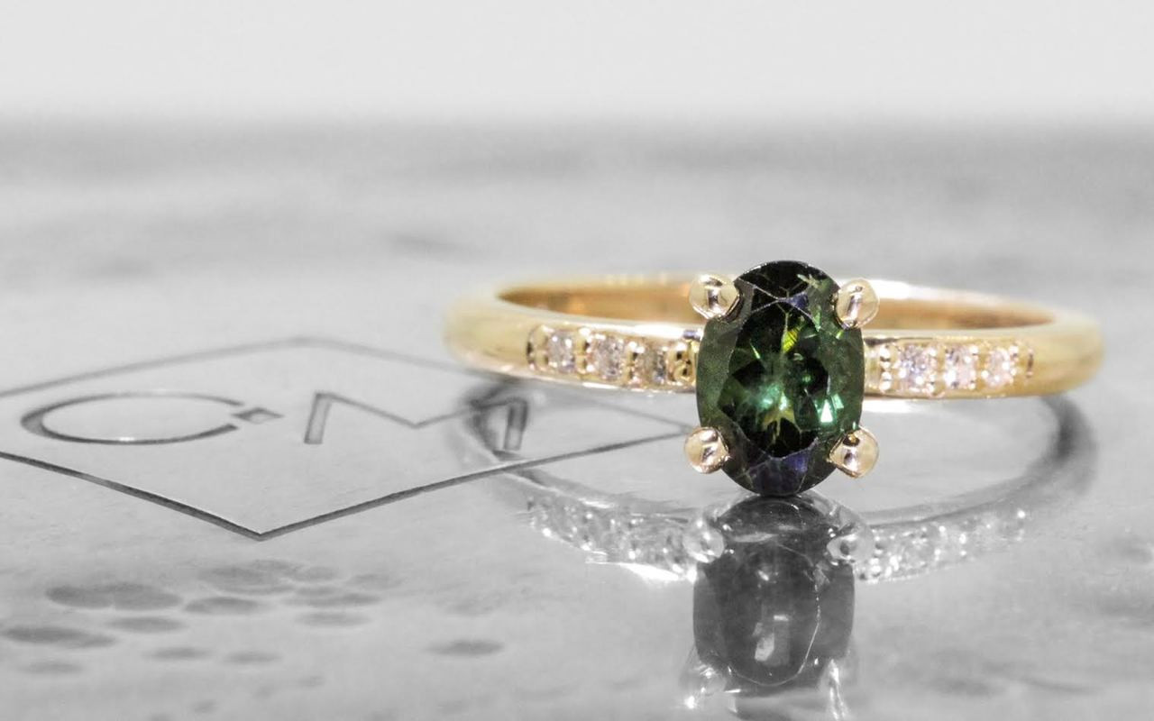 .80 carat green oval faceted tourmaline with six 1.2mm brilliant white diamonds set in 14k yellow gold 1/2 round band. front view on metal background with Chinchar/Maloney logo