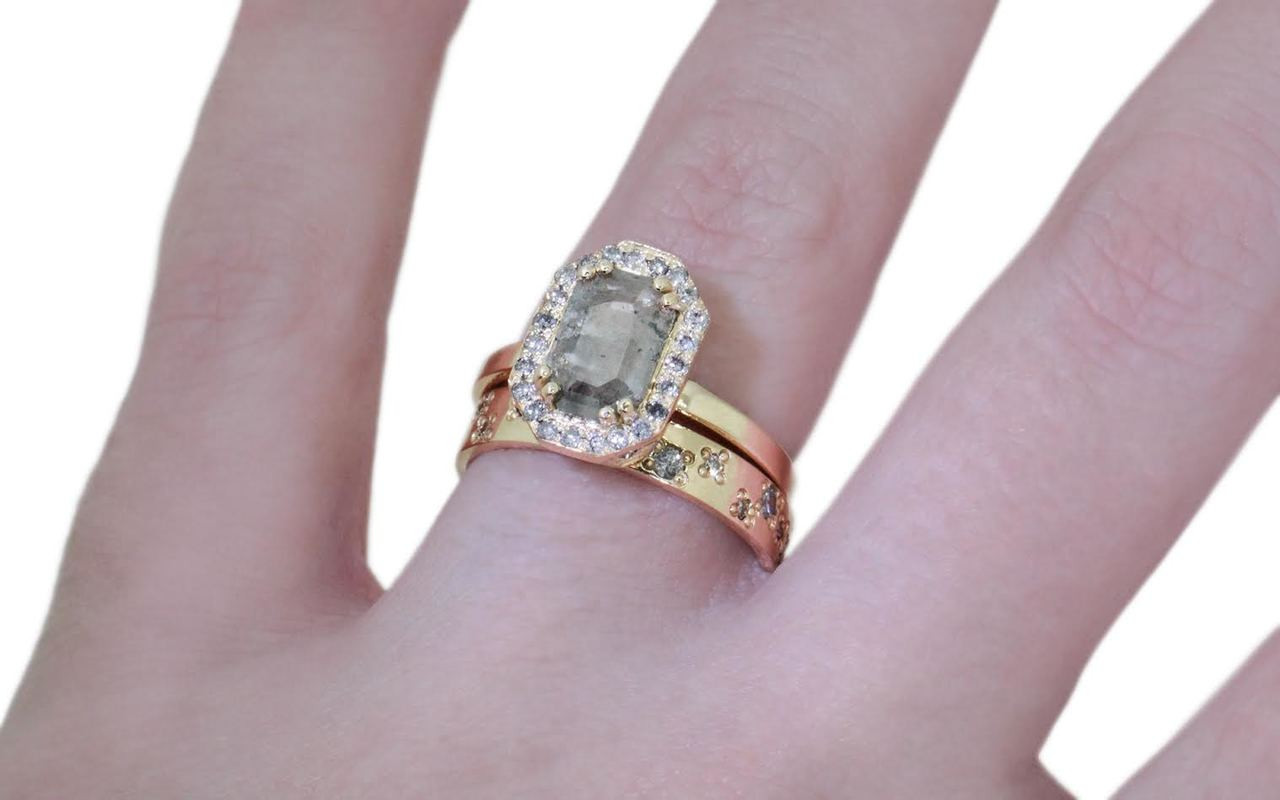 KATLA New Classic 1.07 carat fancy hexagon cut gray diamond prong set in octangular  14k yellow gold setting with brilliant, gray diamonds surround the center diamond in a halo as well as each corner of the setting and each shoulder of the ring.  Shown on hand with organic pave diamond wedding band