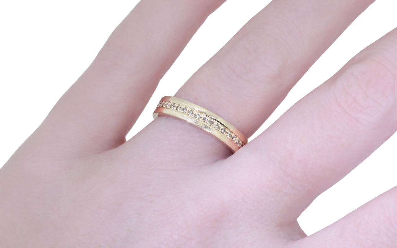 Wedding band in 14k yellow gold with champagne diamonds bead pave set down the center in eternity style.  Modeled on a hand.