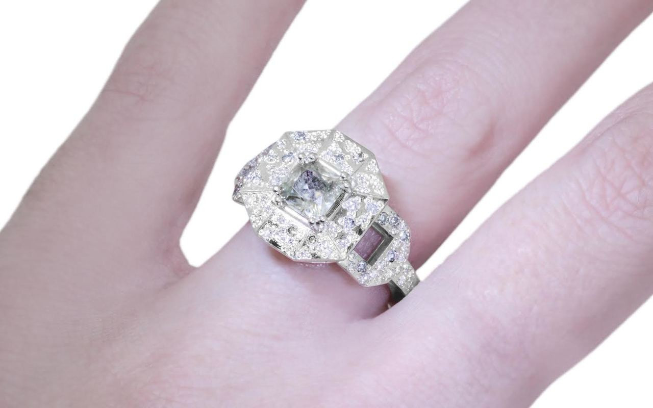 Vesuvio ring in 14k white gold.  1.04 carat  champagne center diamond, cushion brilliant cut.  Halo and buckle band are covered in organic brilliant champagne, gray, white pave.  Modeled on a hand.