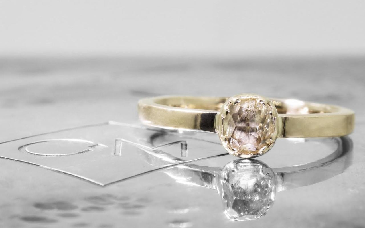 .56 carat  cushion, rose cut champagne bezel set diamond ring set in 14k yellow gold flat band. Front view on metal background with Chinchar/Maloney logo