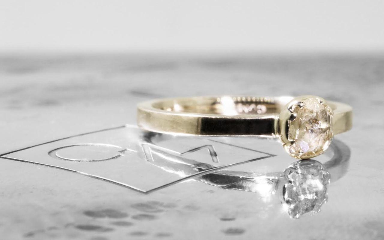 .56 carat  cushion, rose cut champagne bezel set diamond ring set in 14k yellow gold flat band. 3/4 view on metal background with Chinchar/Maloney logo