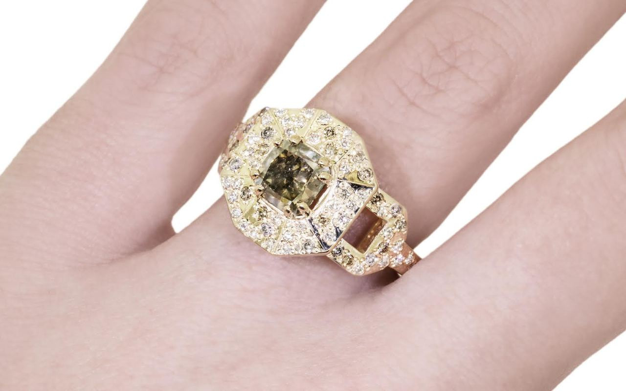 Vesuvio ring in 14k yellow gold.  1.63 carat champagne center diamond, cushion brilliant cut.  Halo and buckle band are covered in organic brilliant champagne, gray, white pave.  Modeled on a hand.