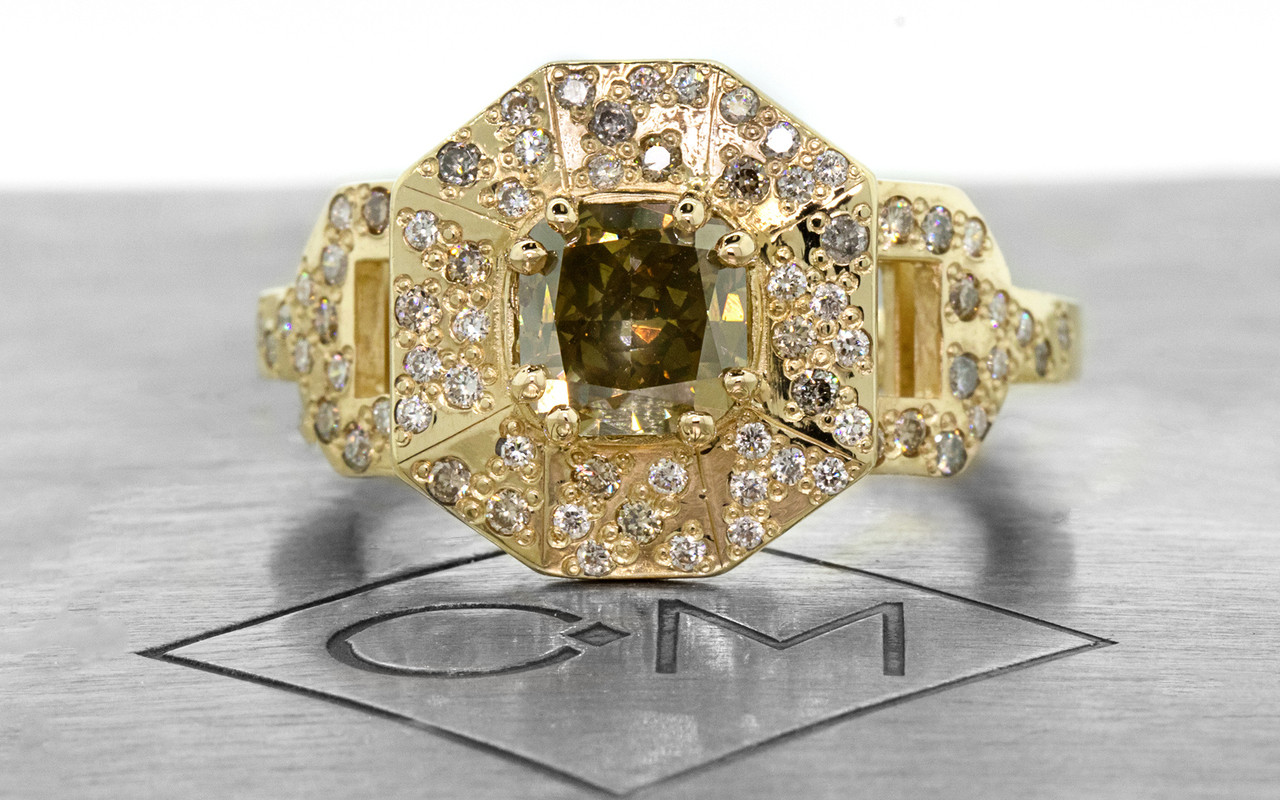 Vesuvio ring in 14k yellow gold.  1.63 carat champagne center diamond, cushion brilliant cut.  Halo and buckle band are covered in organic brilliant champagne, gray, white pave.  Front view on a metal plate with Chinchar/Maloney logo.