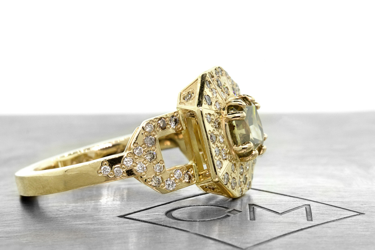 Vesuvio ring in 14k yellow gold.  1.63 carat champagne center diamond, cushion brilliant cut.  Halo and buckle band are covered in organic brilliant champagne, gray, white pave.  Side view on a metal plate with Chinchar/Maloney logo.