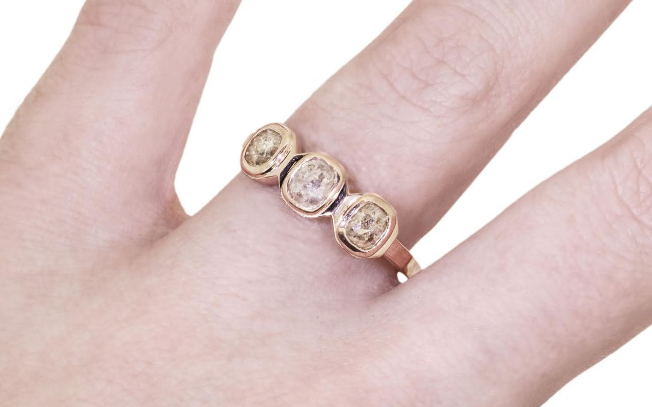 14k rose gold ring with three gray rose cut diamonds bezel set in a rose.  The shape of each setting is octagonal.  Modeled on a hand.