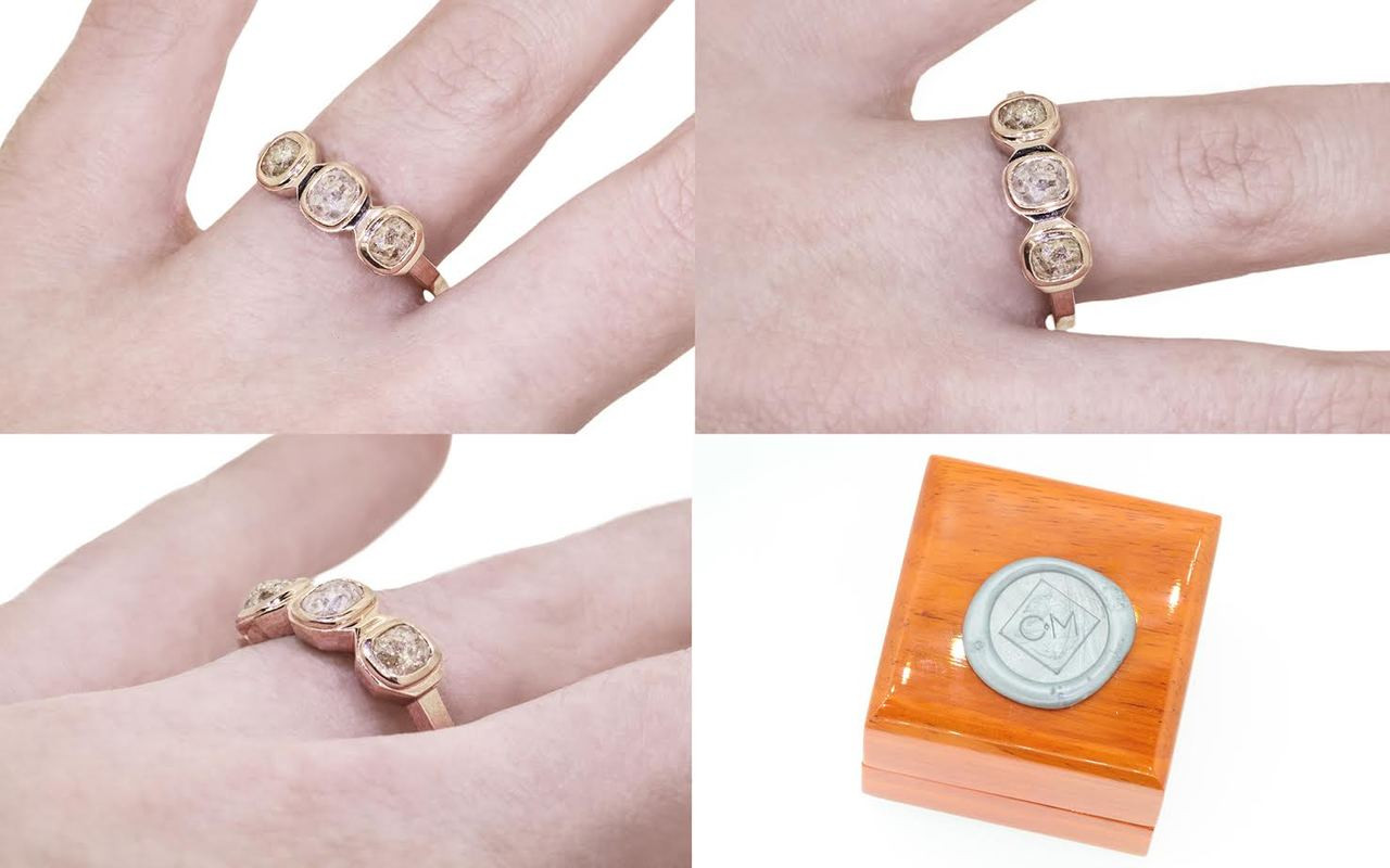 14k rose gold ring with three gray rose cut diamonds bezel set in a rose.  The shape of each setting is octagonal.  Modeled on a hand with wooden ring box with Chinchar/Maloney wax seal logo.