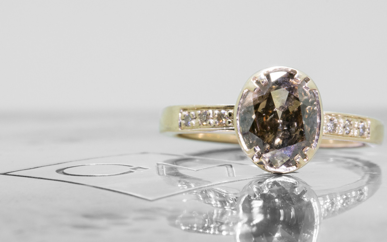 2.17 carat oval, faceted cut deep Cocoa bezel/prong set diamond ring set in 14k yellow gold with six 1.2mm brilliant champagne diamonds set in flat band. Front view on metal background with Chinchar/Maloney logo
