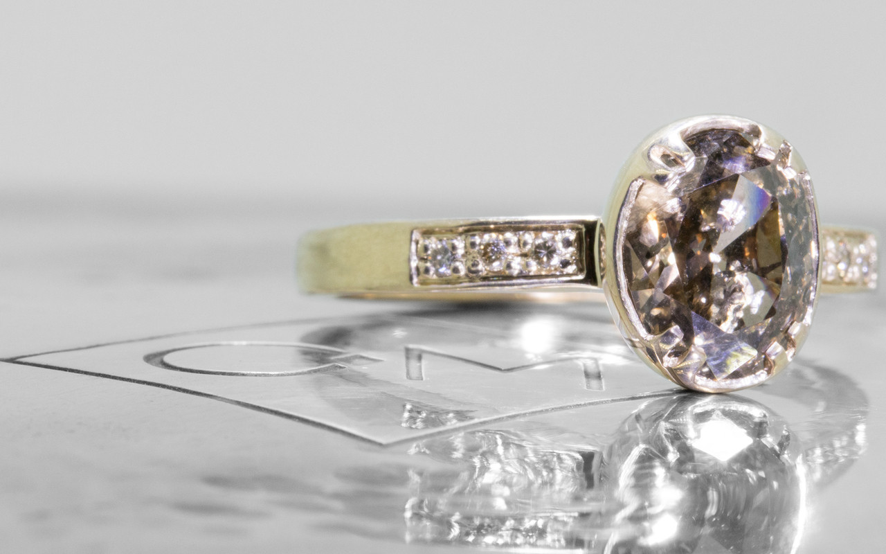 2.17 carat oval, faceted cut deep Cocoa bezel/prong set diamond ring set in 14k yellow gold with six 1.2mm brilliant champagne diamonds set in flat band. 3/4 view on metal background with Chinchar/Maloney logo