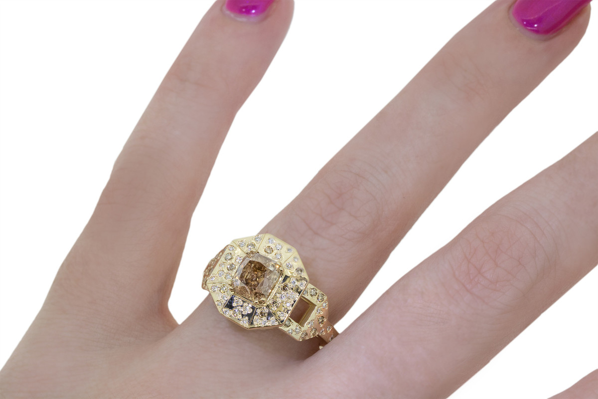 Vesuvio ring in 14k yellow gold.  1.80 carat champagne center diamond, cushion brilliant cut.  Halo and buckle band are covered in organic brilliant champagne, gray, white pave. Modeled on a hand.