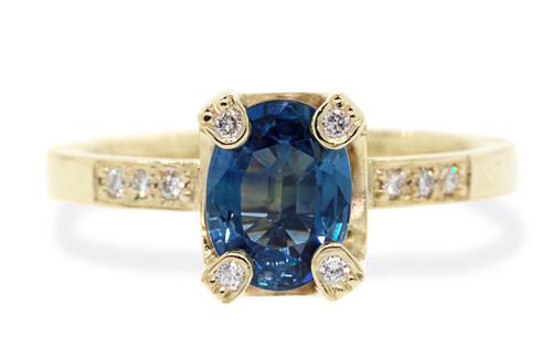 1.79 carat oval, faceted cut blue sapphire with ten 1.2mm brilliant white diamonds set in band and prongs of main setting set in 14k yellow gold flat band. Front view on white background