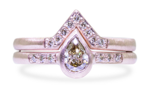 Wedding set in 14k rose gold with .35 carat pear shaped champagne diamond in bezel setting.  Three small, brilliant champagne diamonds are set in the band on each side of the center diamond.  A matching wedding band is stacked on top.  It is triangular and has small brilliant champagne diamonds set in it.  Front view on a white background.