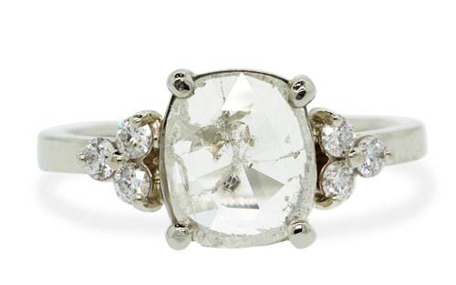 1.54 carat  oval, rose-cut translucent rustic white prong set diamond ring with six 2mm brilliant white diamond clusters on either side of main setting set in 14k white gold flat band. Front view on white background