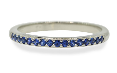 14k white gold wedding band with 16 brilliant cut blue sapphires half way around band on white background