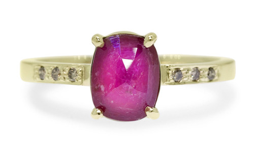1.52 carat oval, faceted cut ruby with six 1.2mm brilliant champagne diamonds in band set in 14k yellow gold flat band. Front view on white background