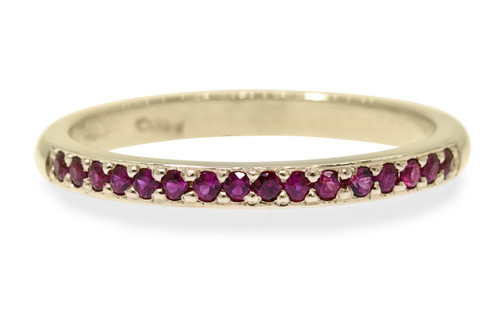 14k yellow gold wedding band with 16 brilliant rubies set half way around band on white back ground