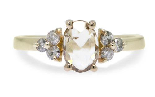 .79 carat oval, rose-cut prong set champagne diamond ring with six 2mm brilliant gray diamond clusters on either side of main setting set in 14k yellow gold flat band. Front view on white background