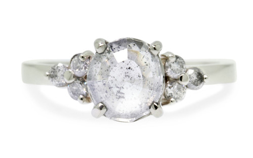 1.61 carat oval, rose-cut glowing salt and pepper prong set diamond ring set in 14k white gold with six 2mm brilliant gray diamonds set in clusters on either side of main setting flat band. Front view on white background
