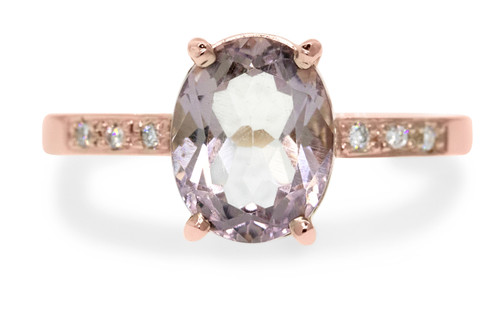 1.99 carat oval faceted cut light pink morganite with six 1.2mm brilliant white diamonds in band set in 14k rose gold flat band. front view on white background