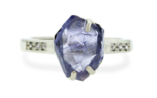 1.96 carat partially hand-cut and polished tanzanite inlaid prong set ring, with six 1.2mm brilliant gray diamonds bead set into 14k recycled white 2.5mm wide gold band. Part of our Refined Rough Collection. Front view on white background
