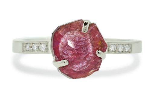 1.68 carat one of a kind partially hand cut deep, saturated color with streaks of inner texture inlaid prong set ruby ring with six 1.2mm brilliant white diamonds bead set into 14k recycled white 2mm flat gold band. Part of our Refined Rough Collection. Front view on white background
