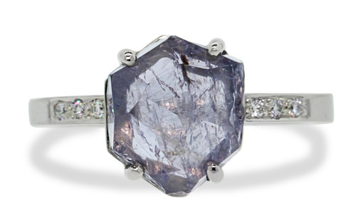 one-of-a-kind, partially hand-cut and polished, 1.96 carat tanzanite ring. prongs in our original design have been inlaid into grooves carved into the gem for a secure and smooth setting. Six 1.2mm brilliant gray diamonds have been bead-set into the band on each side of the tanzanite. 14k recycled white 2mm wide flat gold band. Front view on white background.