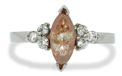 .90ct one of a kind marquise, rose-cut diamond has delicious, vivid peach color. Set into v -caps in 14k recycled white gold with six 2mm brilliant white diamonds set into clusters on either side of main diamond. flat band. Front view on white background