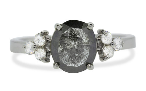1.22 ct diamond has beautiful, inky black color, oval rose cut prong set diamond. Set into 14k recycled white gold 2mm flat band with six 2mm brilliant white diamonds set into clusters in either side of the main diamond. One of a kind. Front view on white background