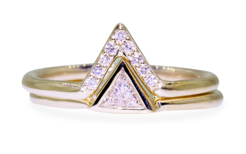 Wedding set in 14k yellow gold with .15 carat trillion white diamond in bezel setting.  A matching wedding band is stacked on top.  It is triangular and has small brilliant white diamonds set in it.  Front view on white background.