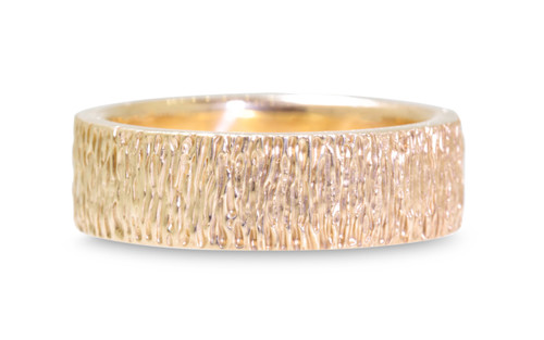 14k yellow gold hand carved textured mens wedding band. On white background
