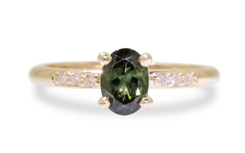 .80 carat green oval faceted tourmaline with six 1.2mm brilliant white diamonds set in 14k yellow gold 1/2 round band. front view on white background