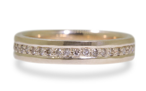 Wedding band in 14k yellow gold with champagne diamonds bead pave set down the center in eternity style.  On white background.