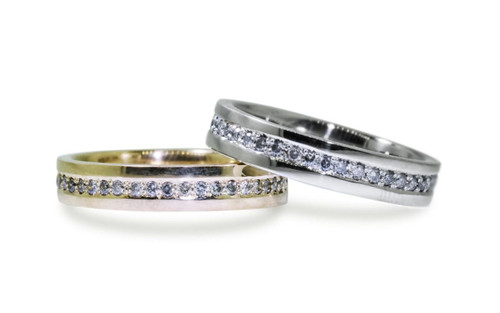 Wedding bands in 14k yellow gold and 14k white gold with gray diamonds bead pave set down the center in eternity style.  On white background.