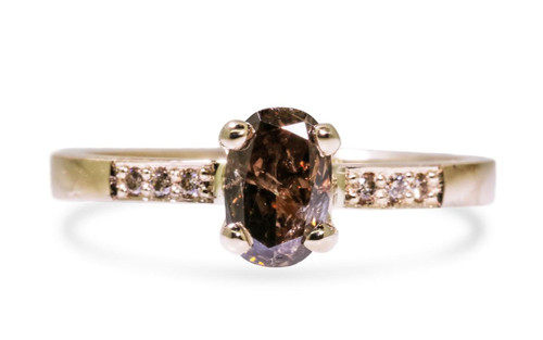 .83 carat oval, faceted cut translucent cognac prong set diamond ring with six 1.2mm brilliant champagne diamonds set into band set in 14k yellow gold flat band. Front view on white background