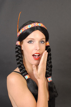 Black plaits with yellow, red and blue patterned band and feather.