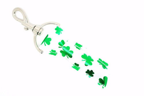 White with green foil shamrocks lip balm holder     This lip balms holder is very durable with a stainless steel hook that is easily attached and unattached to a purse, keys, backpack, or lanyard. This lip balm holder is white with Green foil Shamrocks.  MADE IN THE USA!!