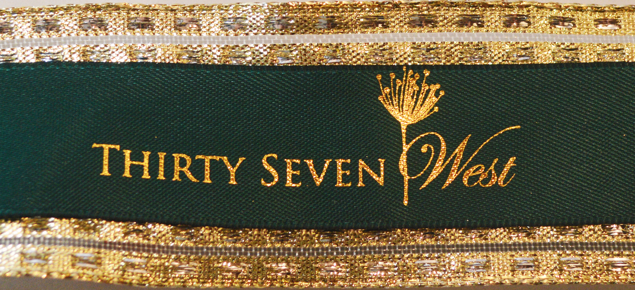 Custom green logo ribbon paired with gold and imprinted in gold