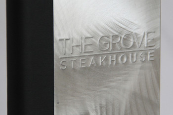 Embossed logo on an aluminum menu cover.