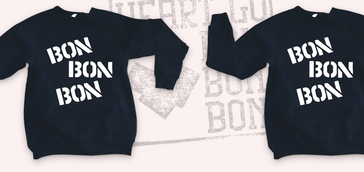 A couple of black t-shirts laying at the bottom of the section on a white surface. Bon Bon Bon is written on them