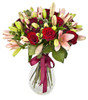 Only You is a luxurious bouquet that includes 6 long stem red roses, pink lilies and mini carnations in a tall clear vase.