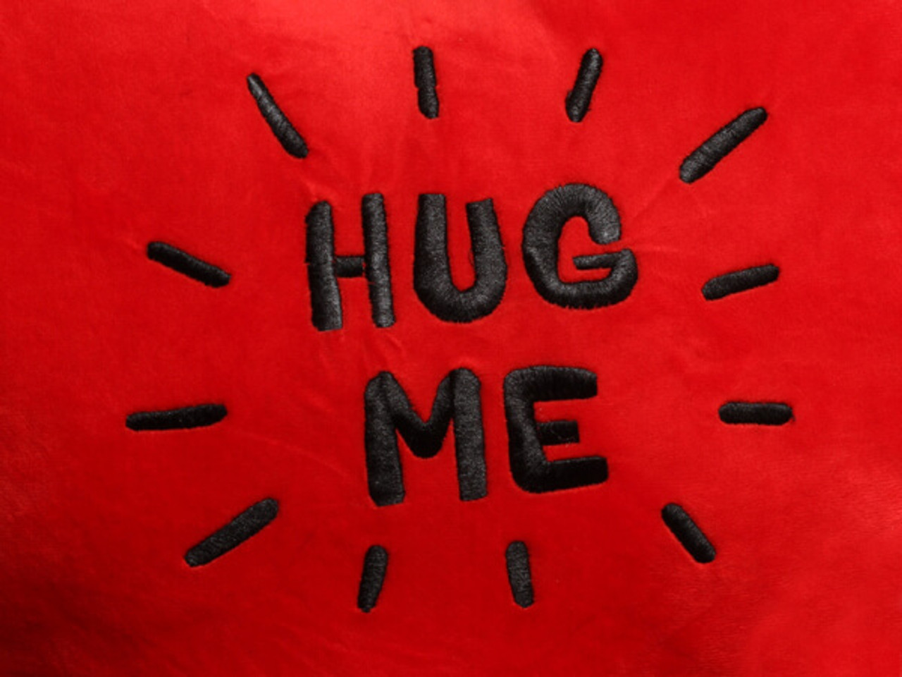 Red heart pillow black embroidery text close-up 'Hug Me'