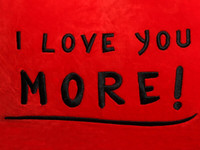 18in red heart pillow black embroidery 'I Love You More!' text close-up