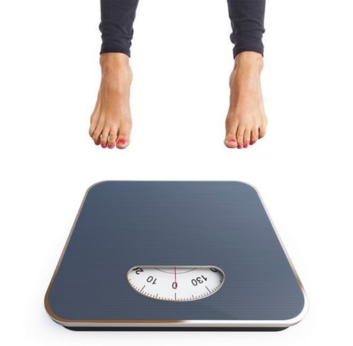 A women's feet floating in the air above a bathroom scale reading 0 lb