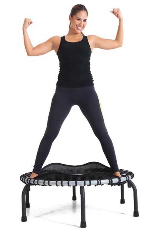 lady in tights making muscles with her arms straddling a JumpSport rebounder fitness trampoline
