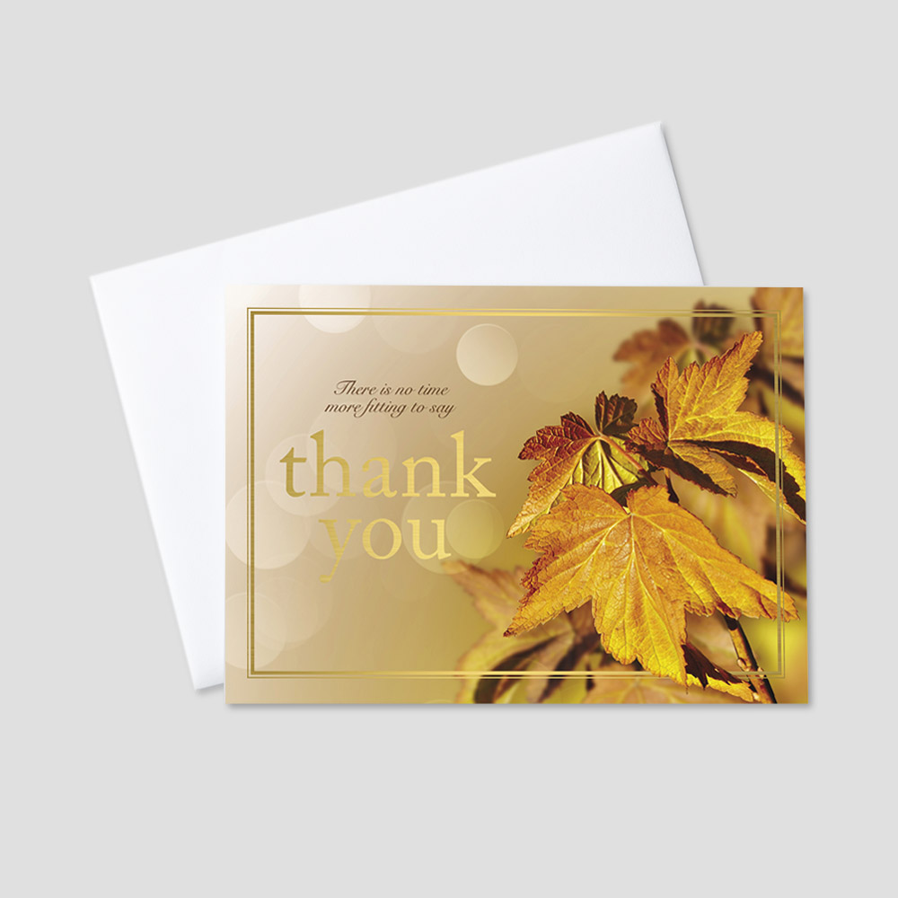 Professional foil printed Thanksgiving greeting card featuring a business Thanksgiving message printed with gold foil situated on amber colored leaves and a gold foil printed border