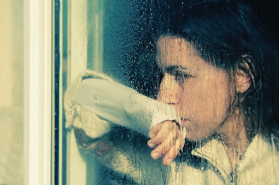 sad women looking out of rainy window.