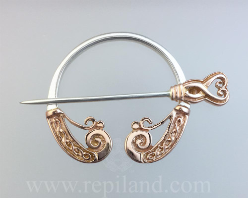 Oronsay Penannular, coiled wave shaped ends with knotwork.