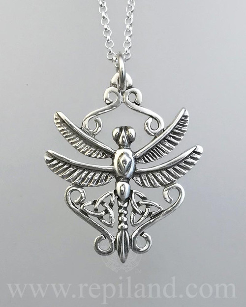 A dragonfly with trinity knots and scrollwork.