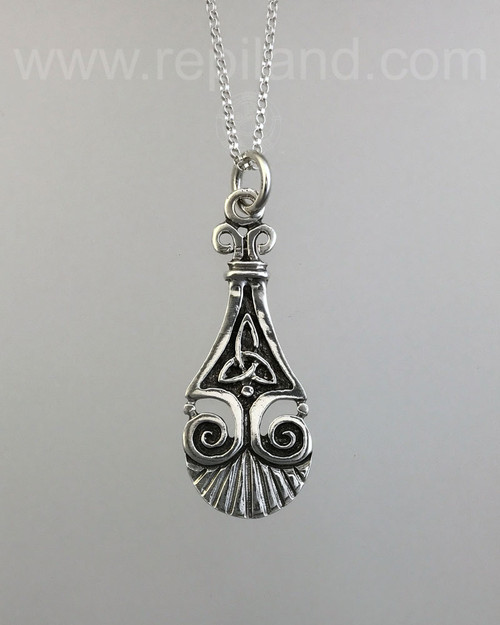 Pendant with a trinity knot, scrolls, beads and a scallop shell edge.