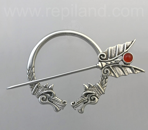 Smiling dragon penannular, pin top has spread wings with a 6mm gemstone.